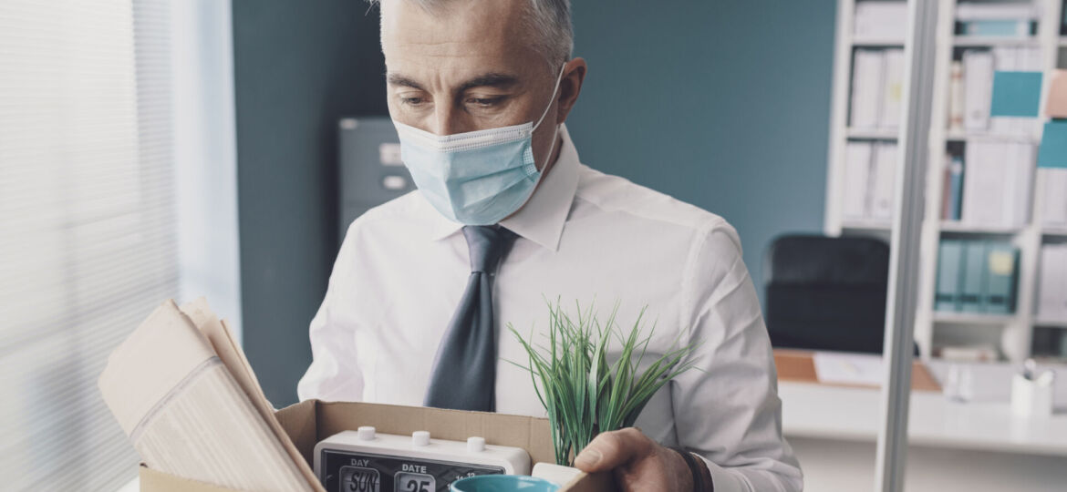 Corporate businessman with face mask leaving the office after losing his job: coronavirus and economic crisis